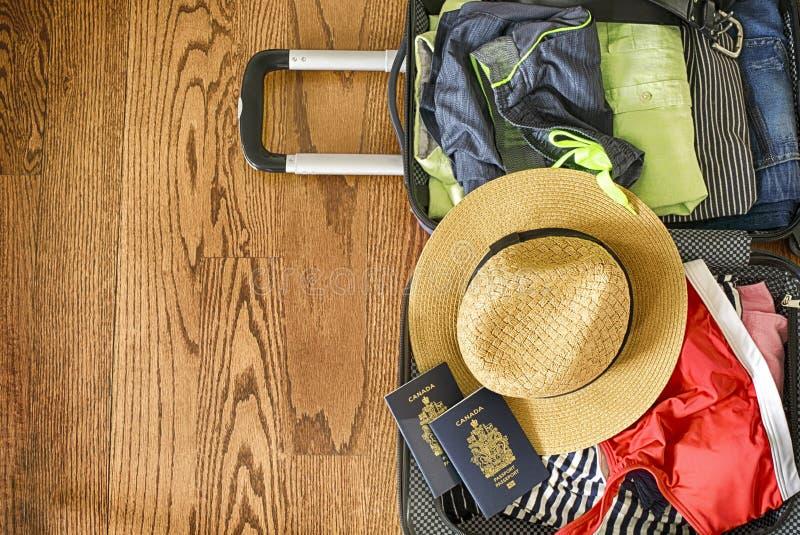 Öppen påse för handelsresande` s med kläder, tillbehör och passet Lopp- och semesterbegrepp arkivbild