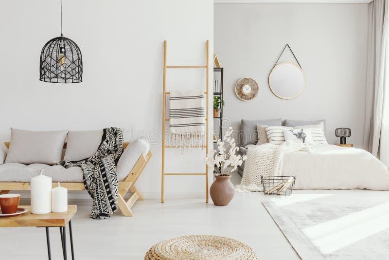 Öppen planlägenhet med bekväm konungformatsäng med kuddar och filten och elegant scandinavian soffa arkivfoton
