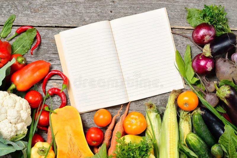 Öppen receptbok med uppsättningen av rå organiska grönsaker på tappningträtabellen royaltyfria foton