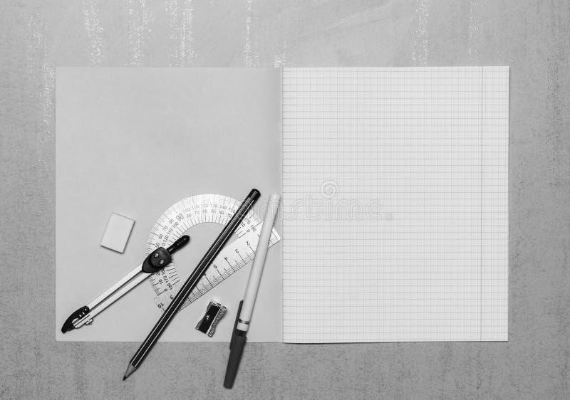 Öppen skolaanteckningsbokåtlöje upp med kopieringsutrymme, kulspetspennan, blyertspennan, radergummit, passare, stålgradskivan oc arkivfoto