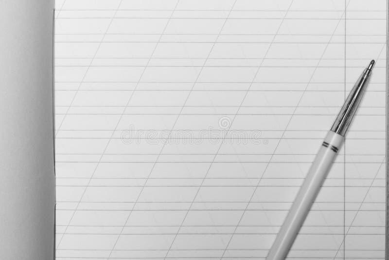 Öppen skolaanteckningsbok i en smal linje med ett snedstreck för att lära upp stavningsåtlöje med kopieringsutrymme och kulspetsp arkivbilder