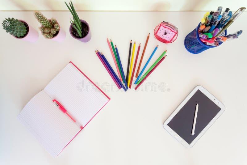 Öppen skrivbok, blyertspennafärgpennor och minnestavla på det vita skrivbordet arkivbilder