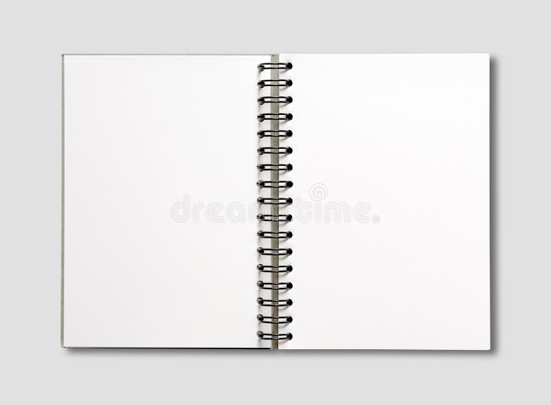 Öppen spiralanteckningsbok för mellanrum som isoleras på grå färger arkivbilder