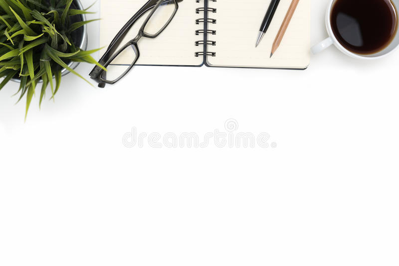 Öppen spiralmellanrumsanteckningsbok med kaffekoppen på det vita skrivbordet royaltyfri foto