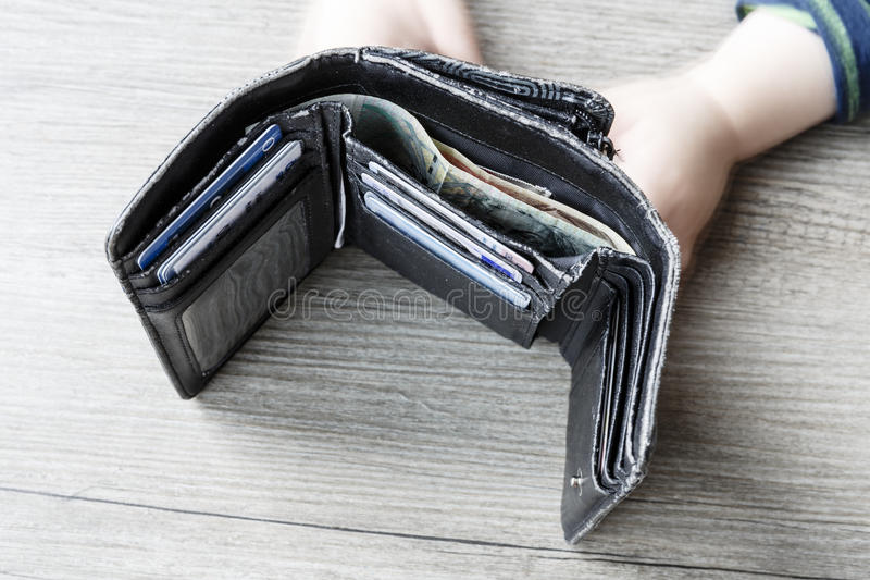 Öppen svart kvinnaplånbok med pengar- och ID-kort och barnhänder arkivfoto