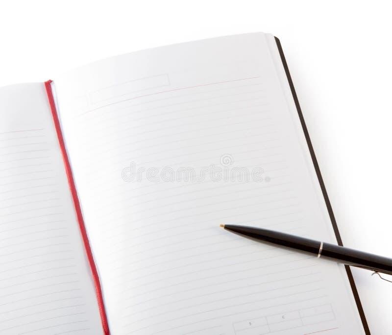Öppen tom bok med linjer, den röda bokmärken, den svarta räkningen och pennan arkivfoton