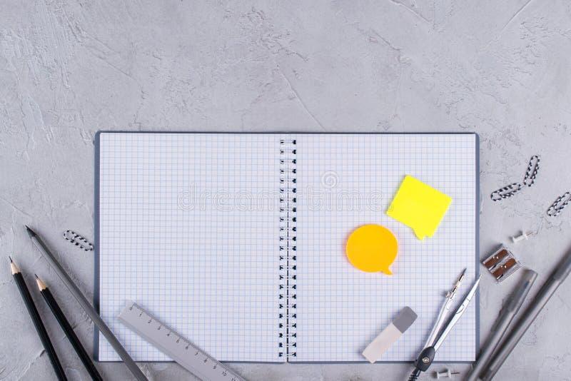Öppen tom spiralanteckningsbok, gråa skolatillförsel på konkret bakgrund Lekmanna- lägenhet fotografering för bildbyråer