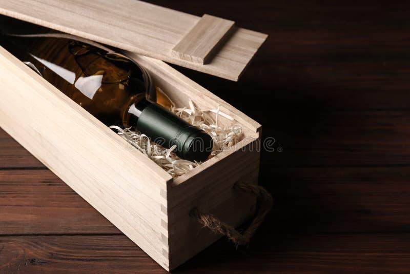 Öppen träspjällåda med flaskan av vin på arkivfoton