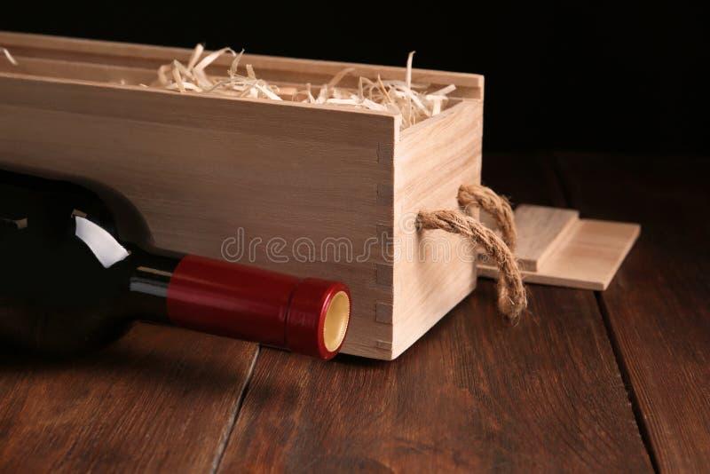 Öppen träspjällåda med flaskan av vin arkivfoton