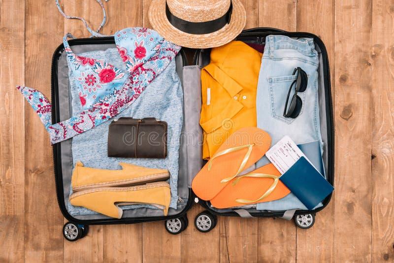 Öppet bagage mycket av kläder för kvinna` s och andra nödvändiga semesterobjekt Ordna till till sommarsemestern royaltyfri fotografi