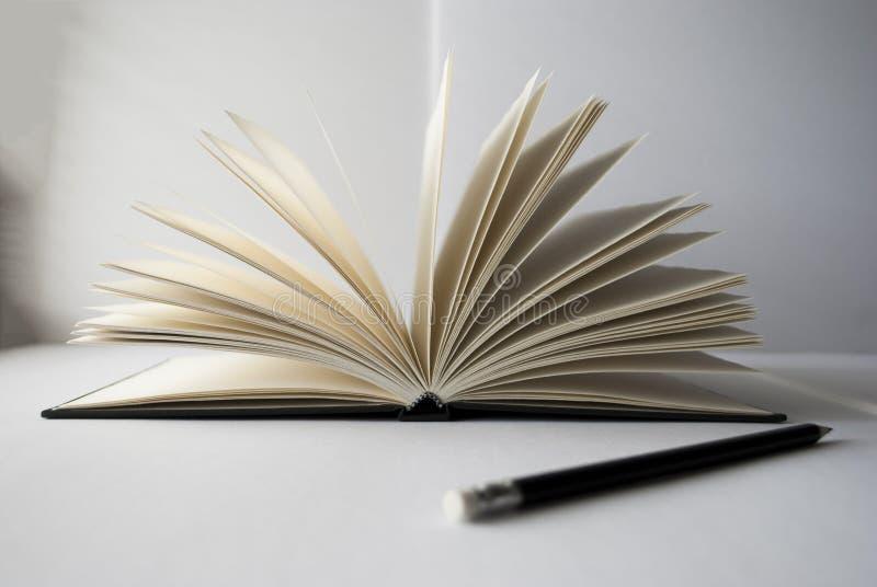 Öppet bok- och blyertspennaslut upp royaltyfria foton