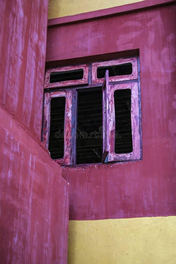 Öppet fönster på den röda väggen arkivfoton