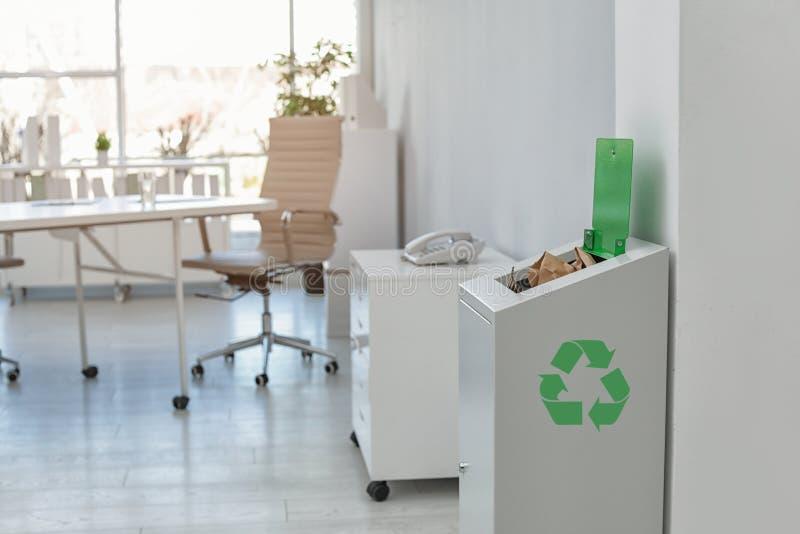 Öppet fullt avfallfack i modernt kontor Förlorad återvinning arkivbild