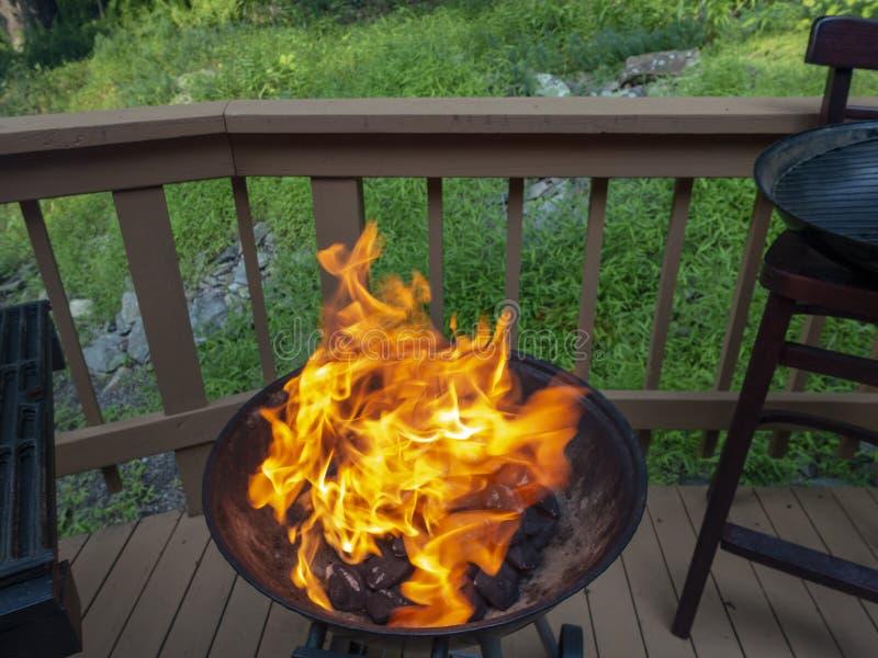 Öppet galler med den stora gula orange flamman som får klar att grilla någon mat på en däcksammankomst för utvändigt land arkivbild