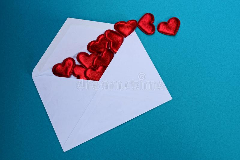 Öppet kuvert för stor vit med röda hjärtor på en blå bakgrund arkivfoto