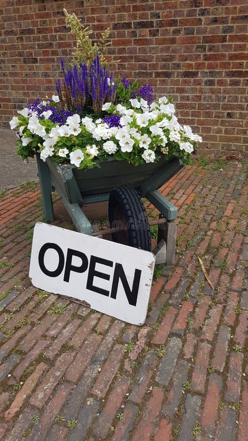 Öppet tecken bredvid en laden skottkärra för blomma royaltyfria foton