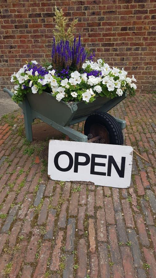 Öppet tecken bredvid en laden skottkärra för blomma arkivbilder