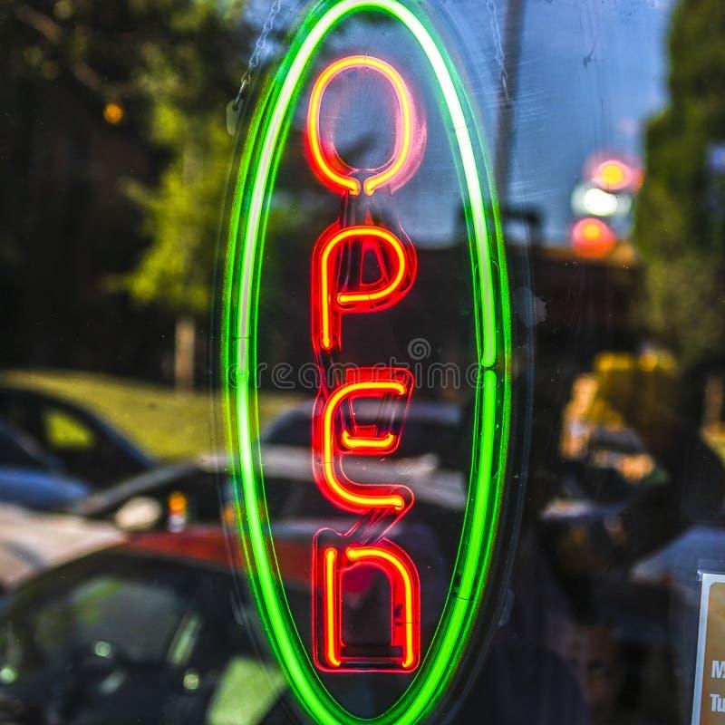 Öppet tecken för neon på en glass dörr med reflexioner royaltyfri bild
