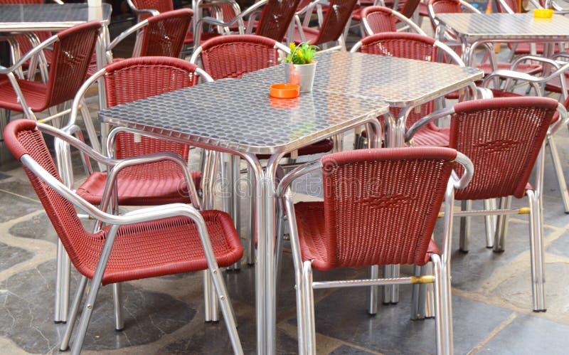Öppet tomt gatakafé, tabeller och stolar med metallramen och vide- möblemang, selektiv fokus och närbild fotografering för bildbyråer