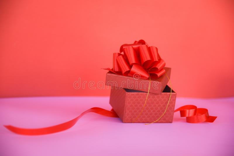 Öppet utrymme för kopia för gåvaask rött på den rosa/röda närvarande asken med den röda bandpilbågen för gåva royaltyfri bild