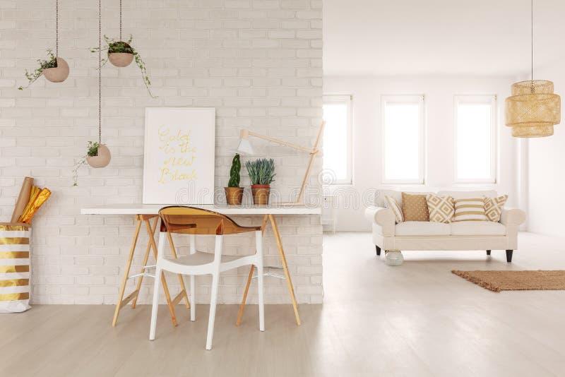 Öppet utrymmevardagsruminre i verkligt foto med den vita soffan med kuddar i bakgrunden, skrivbordet med affischen och växtstandi fotografering för bildbyråer