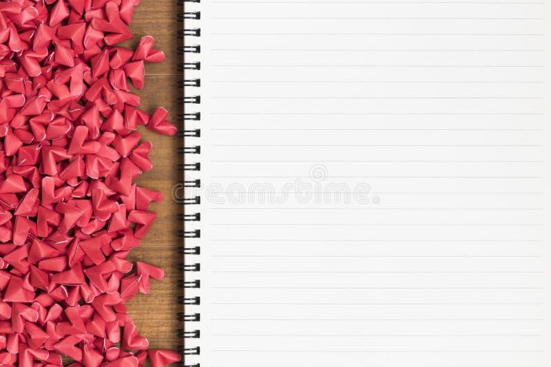 Öppna anmärkningsboken för den tomma sidan med små röda pappers- hjärtor arkivfoton
