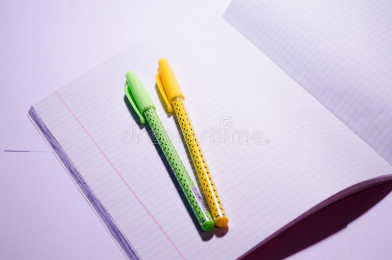 Öppna anteckningsbok Öppna anteckningsbok med pennor Öppna en bärbar dator med skoltillbehör i fyrkant Office Chancellery Rensa c arkivbild