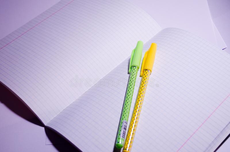 Öppna anteckningsbok Öppna anteckningsbok med pennor Öppna en bärbar dator med skoltillbehör i fyrkant Office Chancellery Rensa c royaltyfria bilder