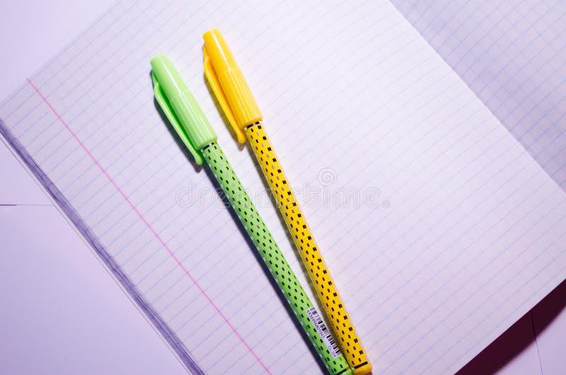 Öppna anteckningsbok Öppna anteckningsbok med pennor Öppna en bärbar dator med skoltillbehör i fyrkant Office Chancellery Rensa c royaltyfri foto