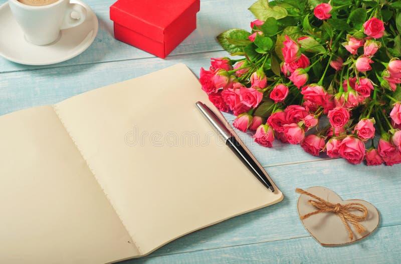Öppna anteckningsboken med tomma sidor med buketten av rosor arkivbilder