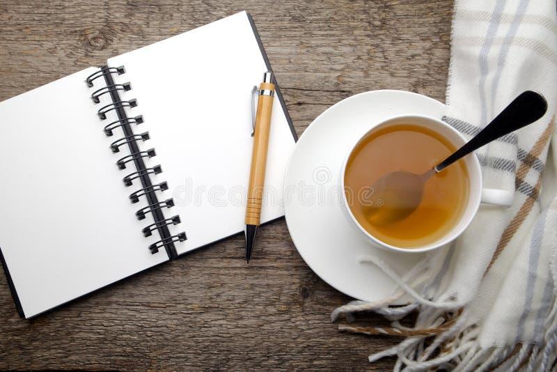 Öppna anteckningsboken och kopp te arkivbilder