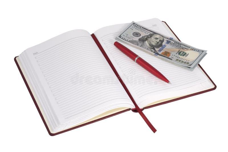 Öppna anteckningsboken och pengar arkivbild