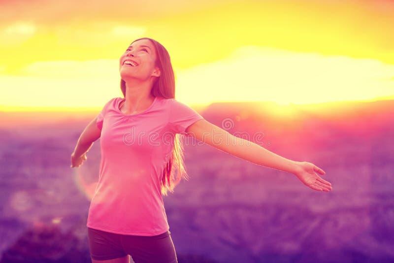 Öppna armar för frihetswellnesskvinna i solnedgång royaltyfri bild
