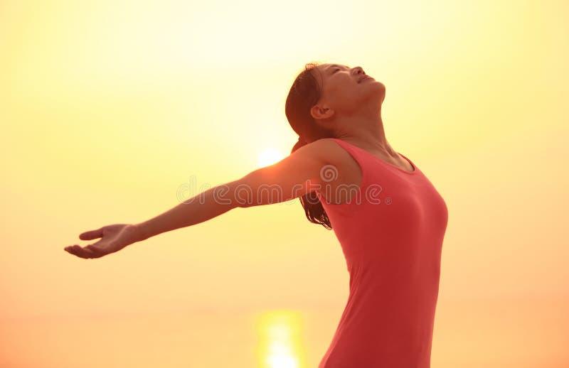 Öppna armar för kvinna på stranden royaltyfria bilder