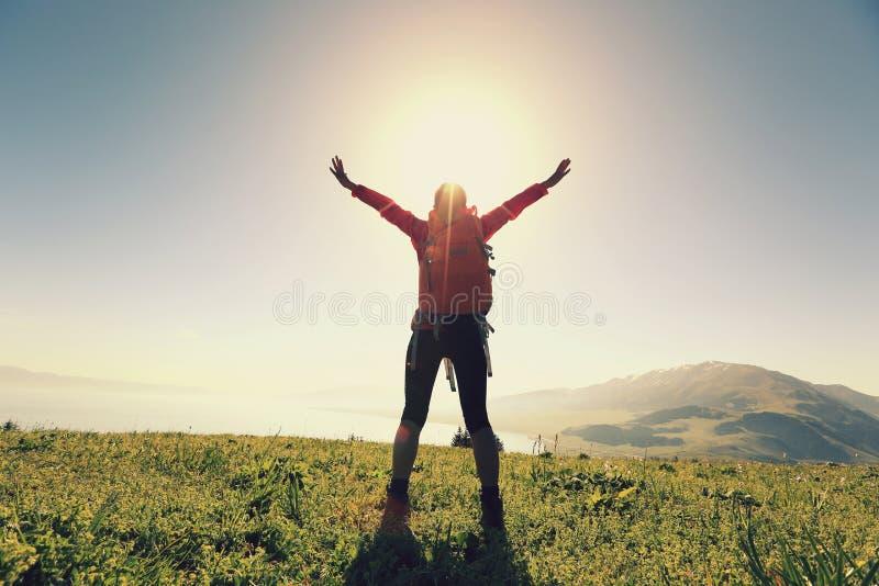 Öppna armar för lyckad kvinnafotvandrare på bergmaximum royaltyfri bild