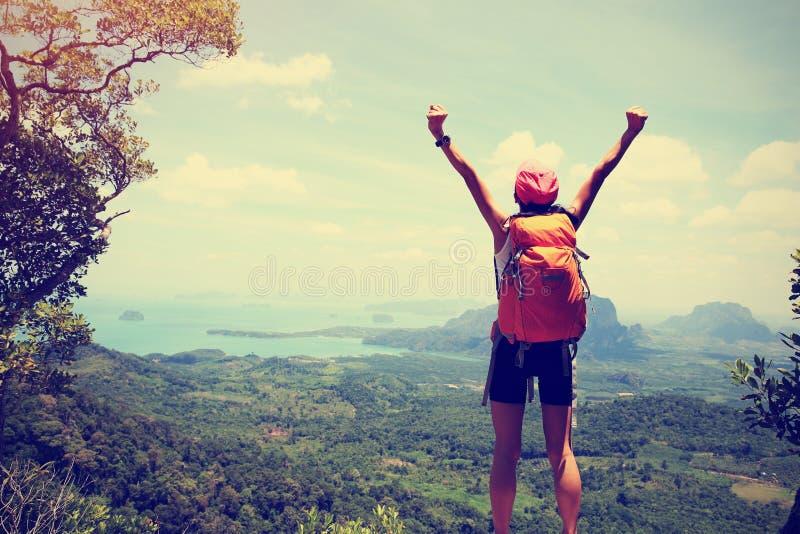 Öppna armar för lyckad kvinnafotvandrare på bergmaximumet arkivbild