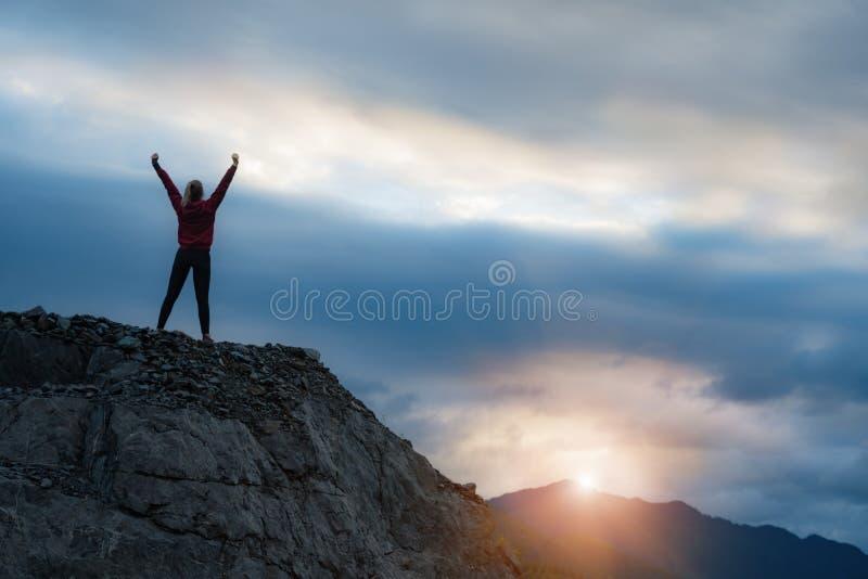 Öppna armar för lyckad kvinnafotvandrare på klippkanten för soluppgångbergöverkant royaltyfri foto