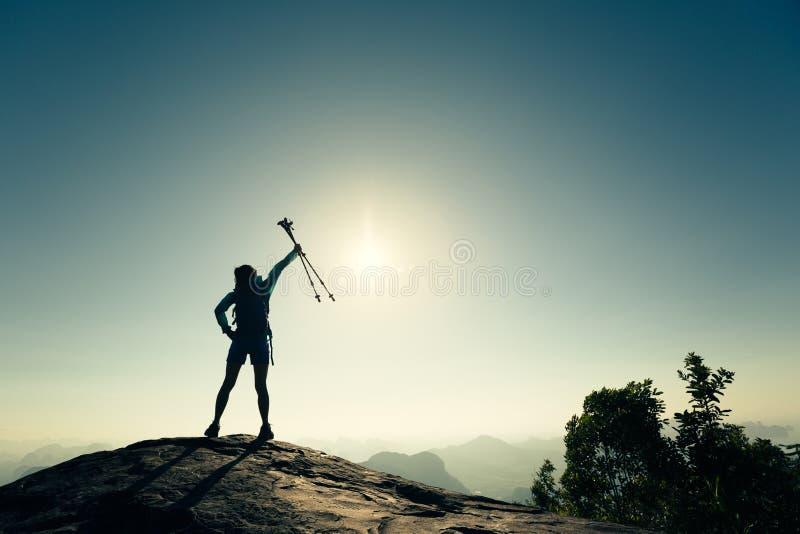 Öppna armar för lyckad kvinnafotvandrare på soluppgångbergöverkant royaltyfri bild
