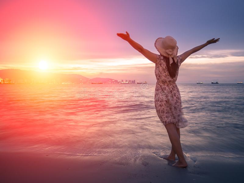 Öppna armar för stark förtroendekvinna under soluppgången på sjösidan arkivbilder