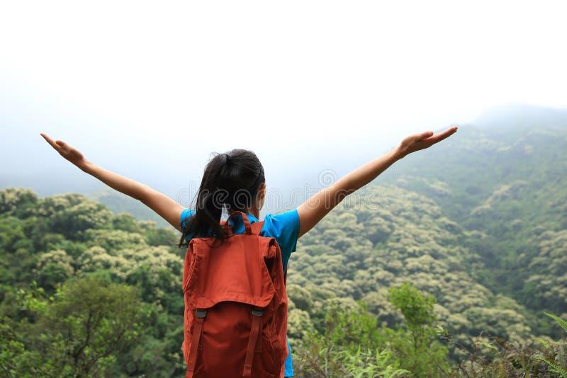 Öppna armar för ung asiatisk kvinna till vårskogen arkivbild