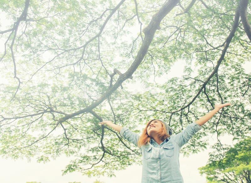 Öppna armar för ung kvinna som står i ny vårgrönska med henne royaltyfri bild