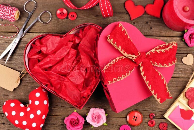 Öppna asken för gåvan för valentindagen den hjärta formade med ramen mot trä arkivbild
