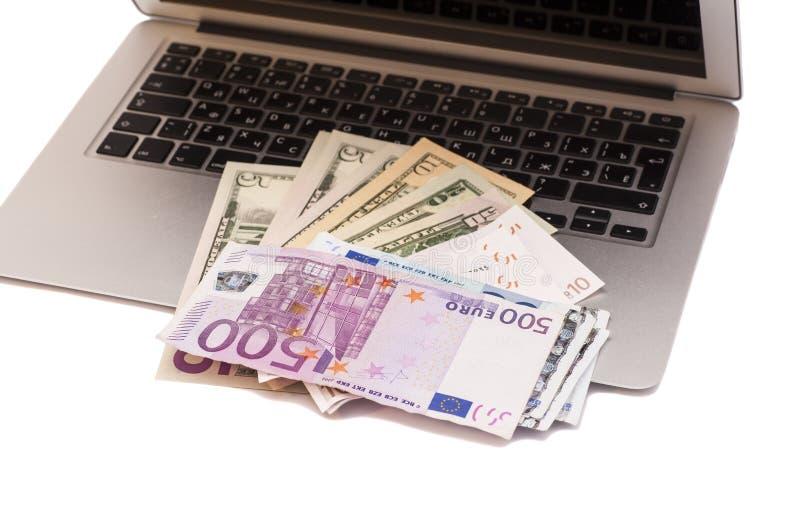 Öppna bärbara datorn med dollar- och europengar fotografering för bildbyråer