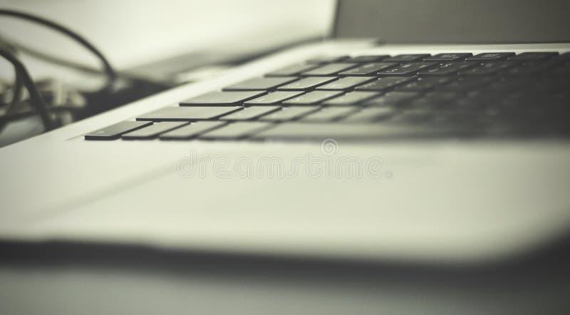 Öppna bärbara datorn med tillbehör av smartphonen och grejen, på det gamla träskrivbordet med härligt ljus fotografering för bildbyråer