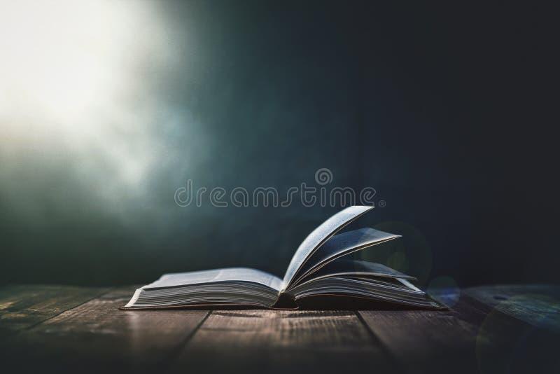 Öppna bibeln med ett ljus som kommer från ovannämnt på ett träskrivbord royaltyfri bild