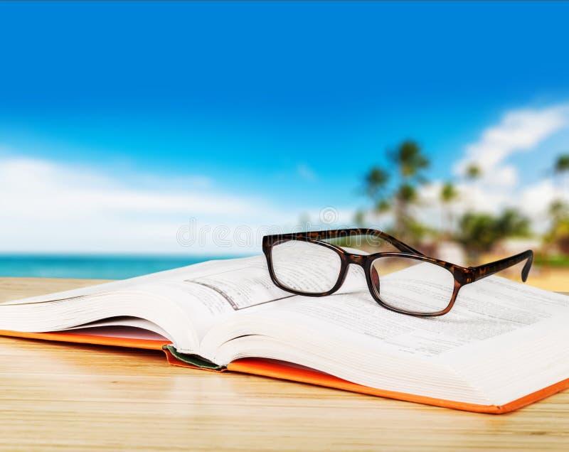 Öppna bok och exponeringsglas, närbildsikt royaltyfria foton