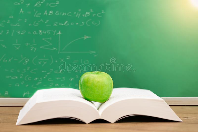 Öppna boken med det gröna äpplet i begreppsutbildning arkivfoto