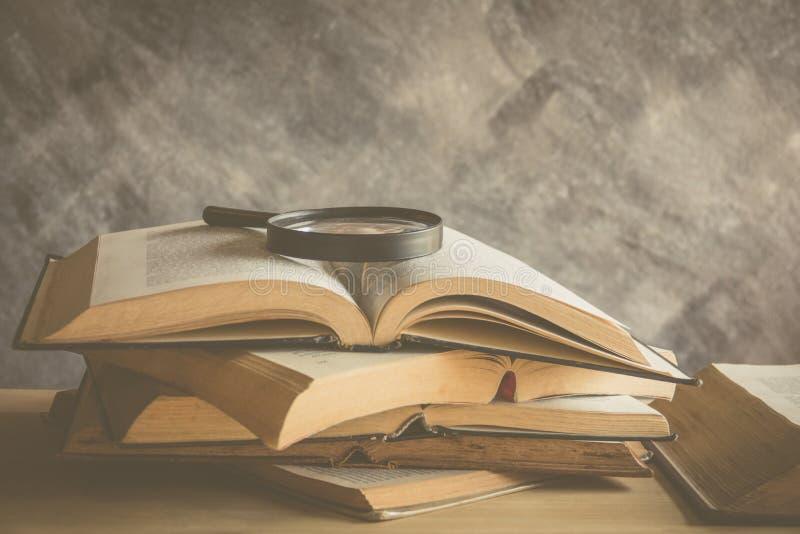öppna boken med läs- exponeringsglas i bokhyllan arkivbilder