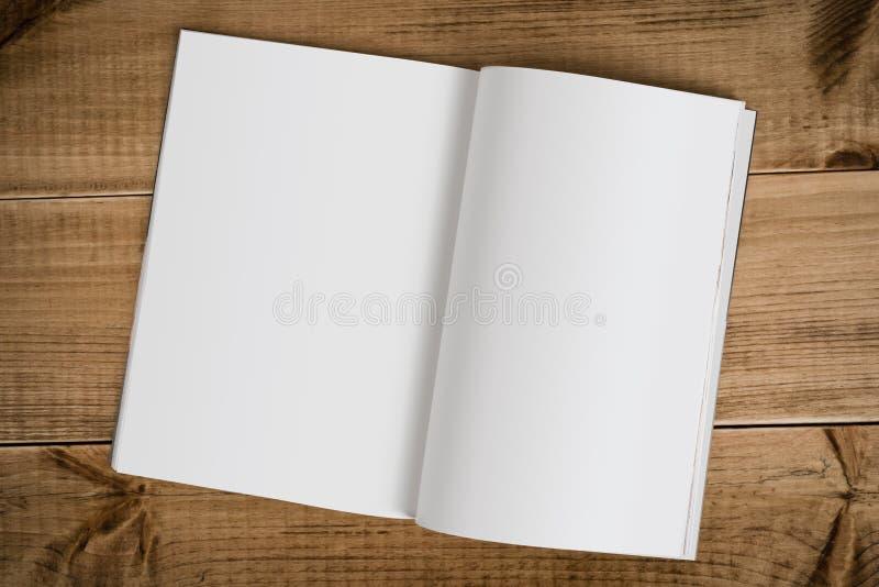 Öppna boken med tomma sidor på trätabellbakgrund royaltyfria bilder