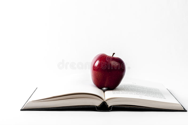 Öppna boken och ett äpple royaltyfria bilder